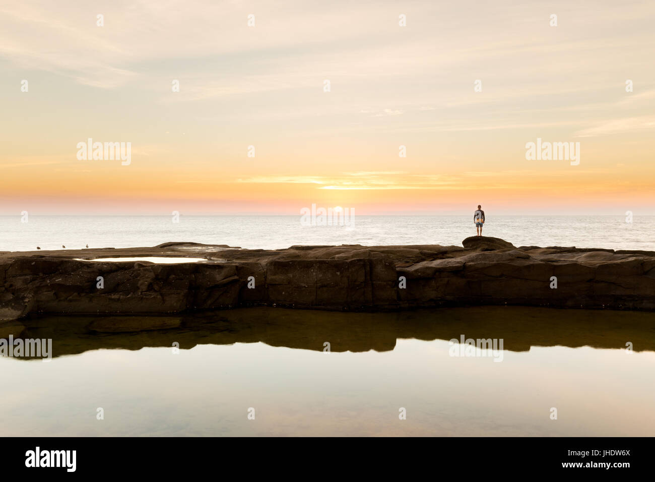 A silhouetted person watches the sunrise over the ocean on a beautiful coastline in Australia. - Stock Image