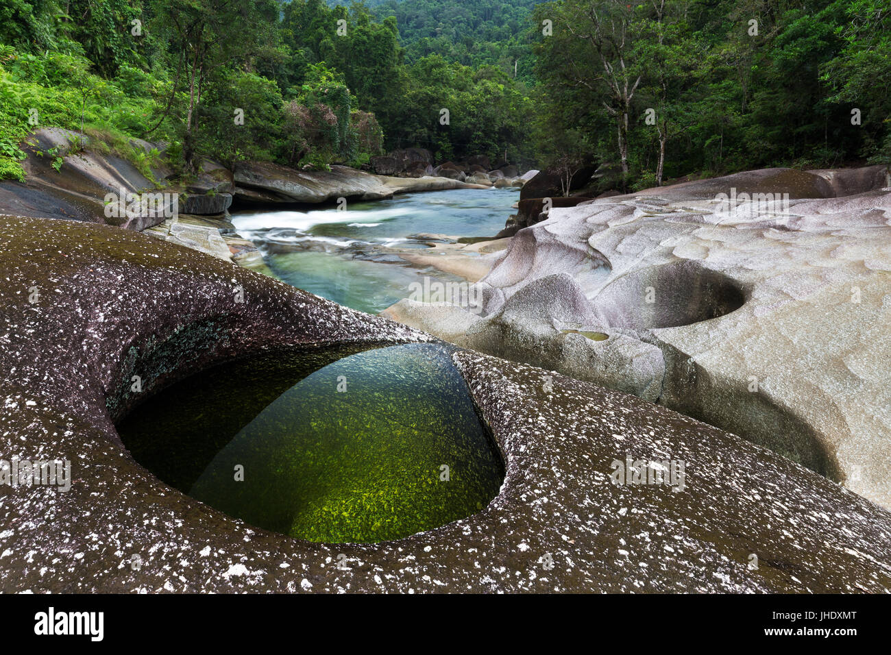 A clear emerald pool in granite rocks beside a river edged by lush tropical rainforest. - Stock Image