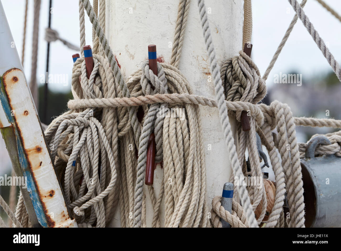 sail ropes tied up to the mast on a sailing ship - Stock Image