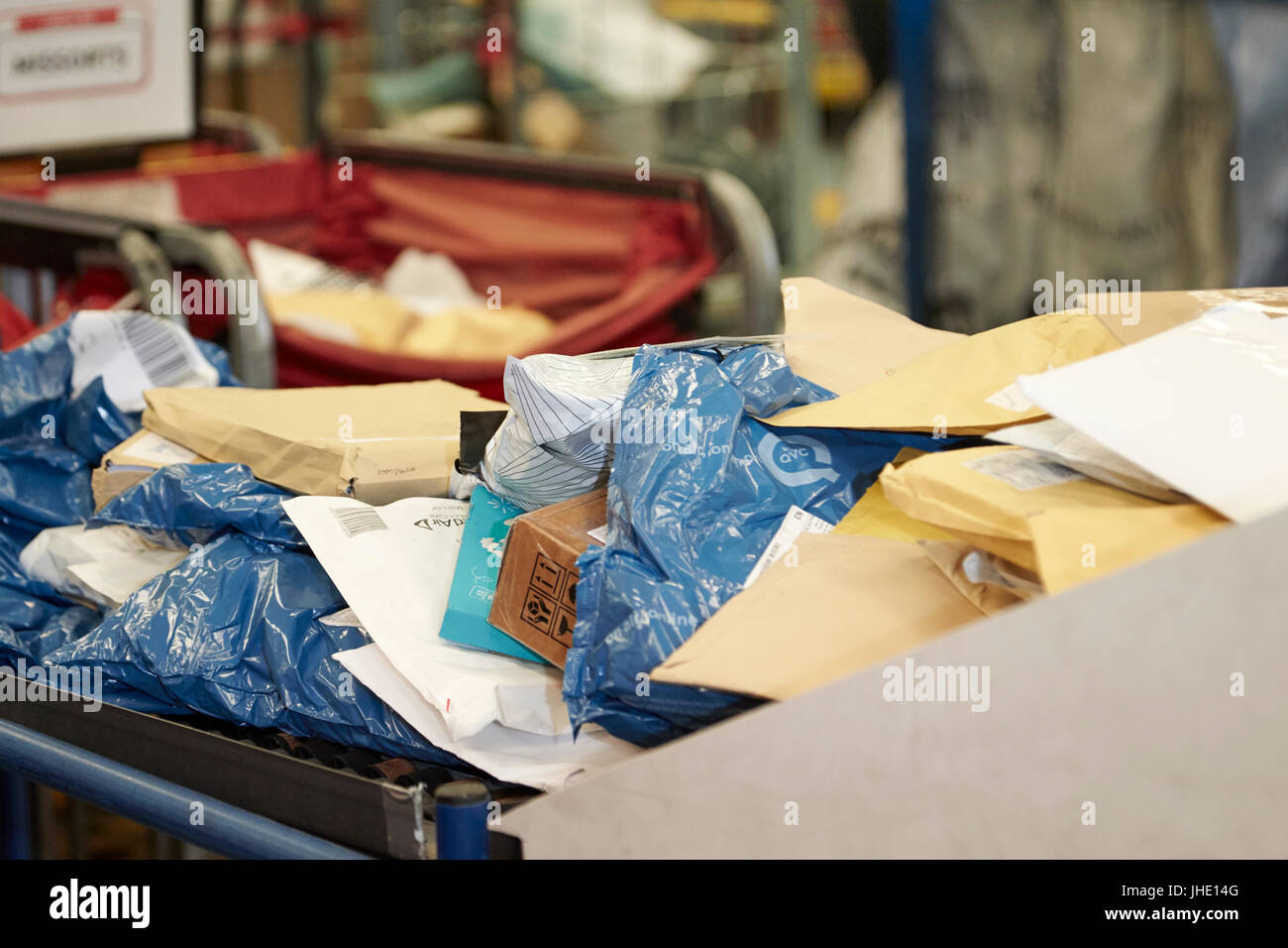 mailing postal bags small parcels and envelopes on conveyor belt at royal mail delivery office - Stock Image