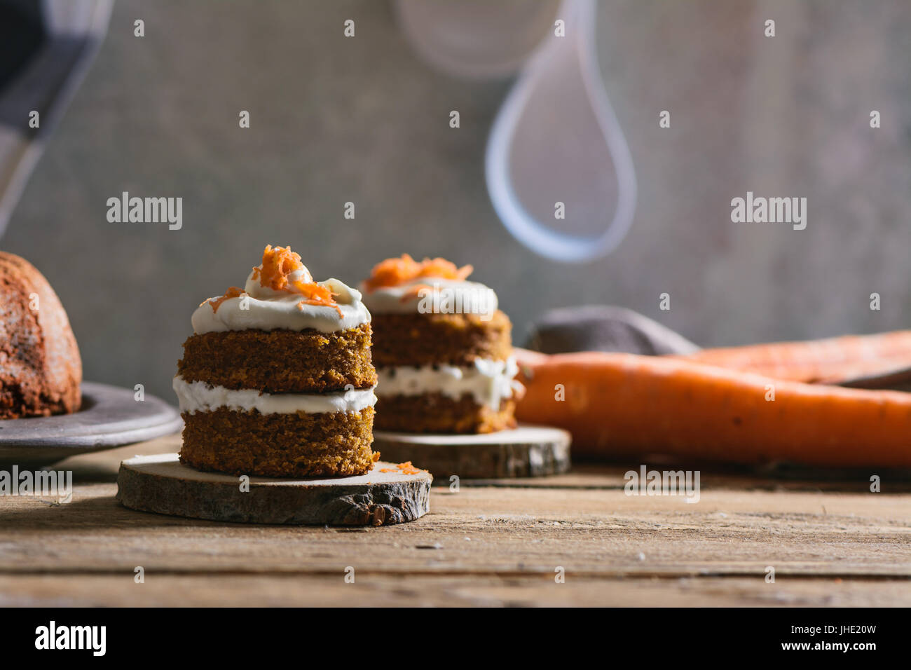 Mini carrot cake, stuffed with cream cheese, on rustic wood plate, close up Stock Photo