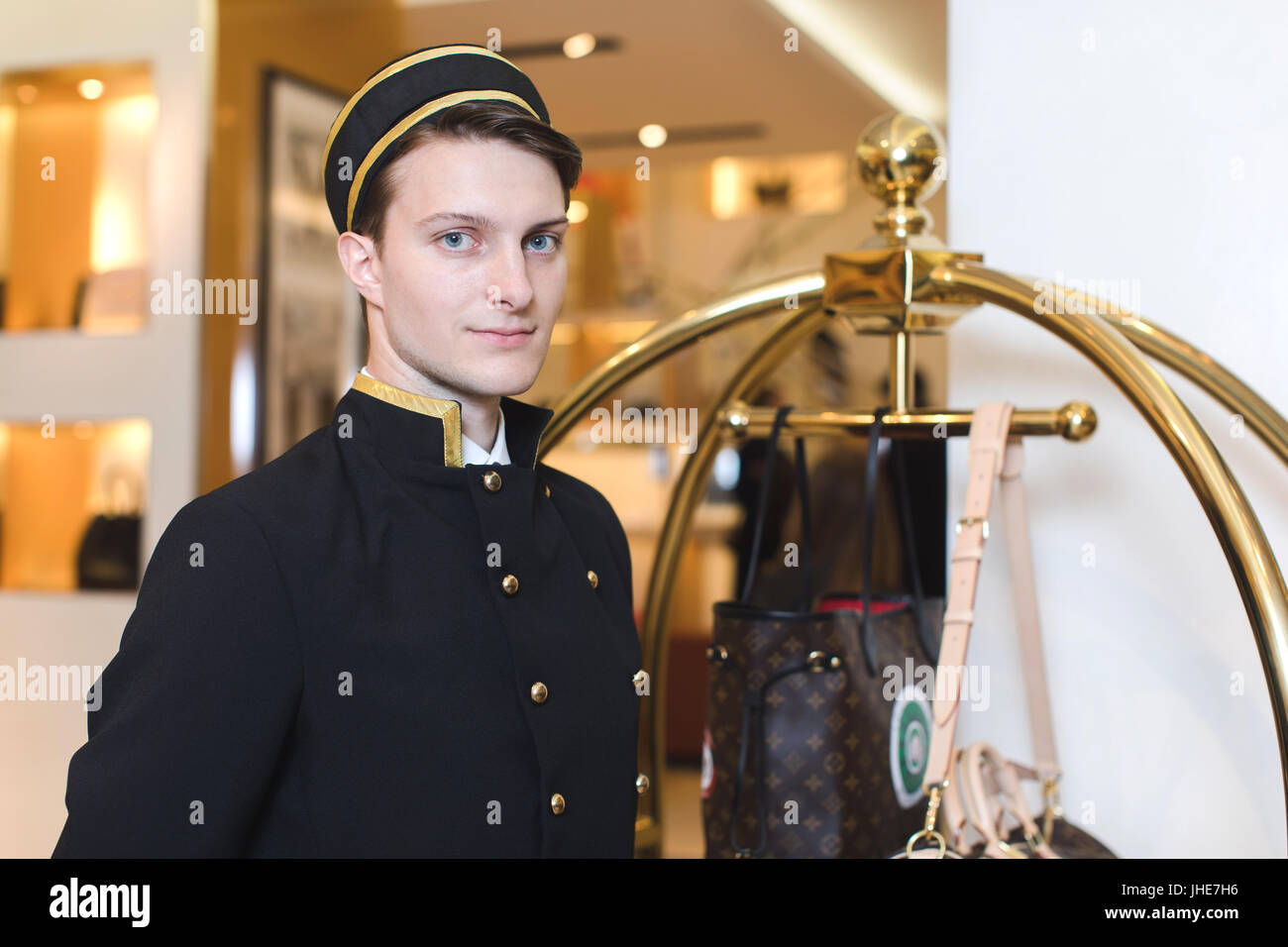 Smiling man in bellboy uniform standing with luggage cart - Stock Image