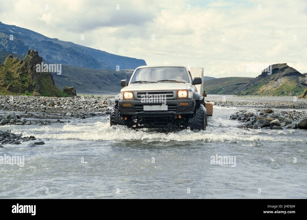 Car pulling trailer and crossing river in Iceland - Stock Image