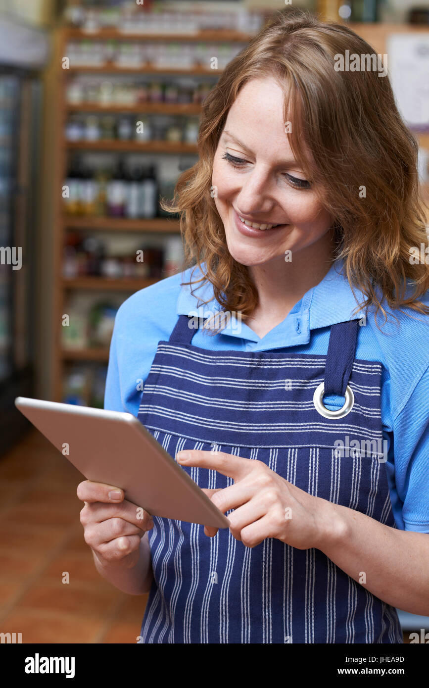 Delicatessen Owner In Store With Digital Tablet - Stock Image