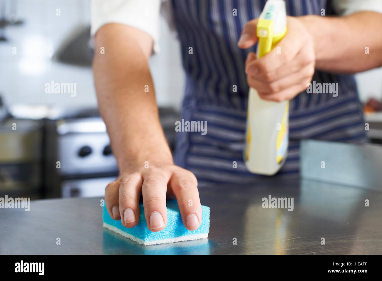 Close Up Of Worker In Restaurant Kitchen Cleaning Down After Service - Stock Image