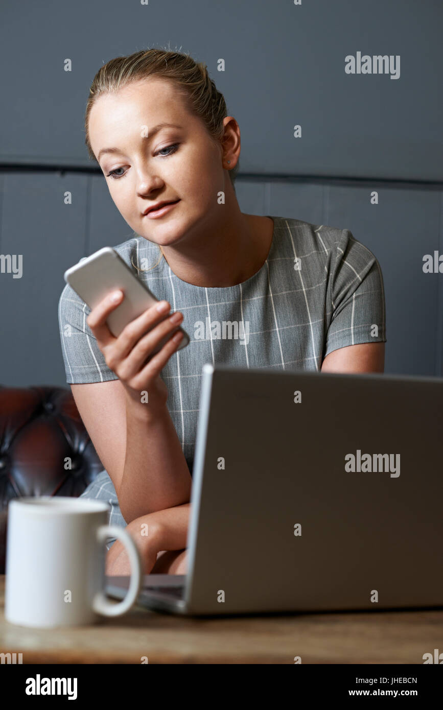 Businesswoman With Mobile Phone Working On Laptop In Internet Cafe - Stock Image