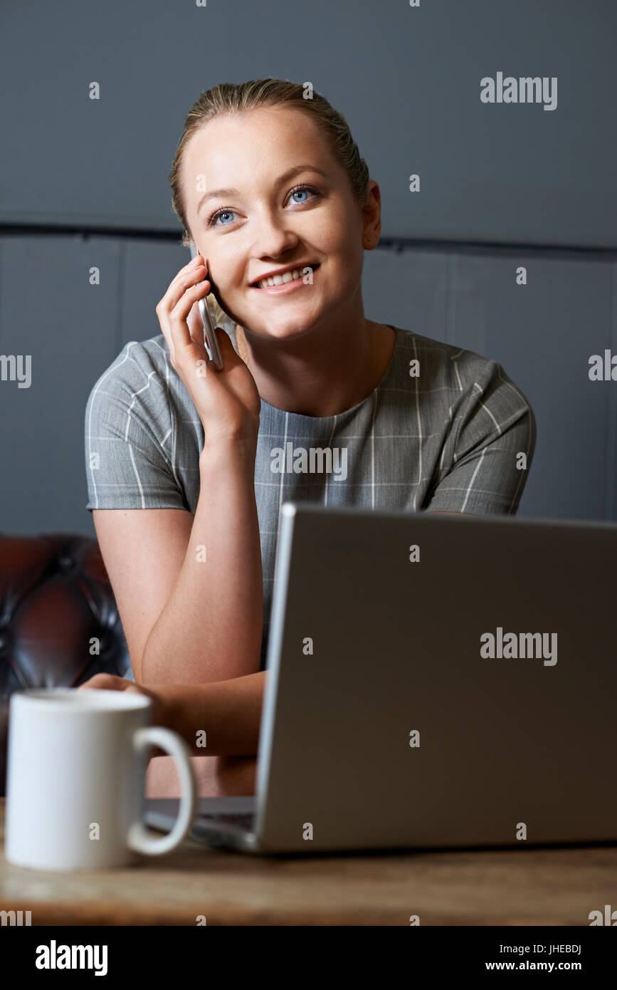 Businesswoman Talking On Mobile Phone Working On Laptop In Internet Cafe - Stock Image