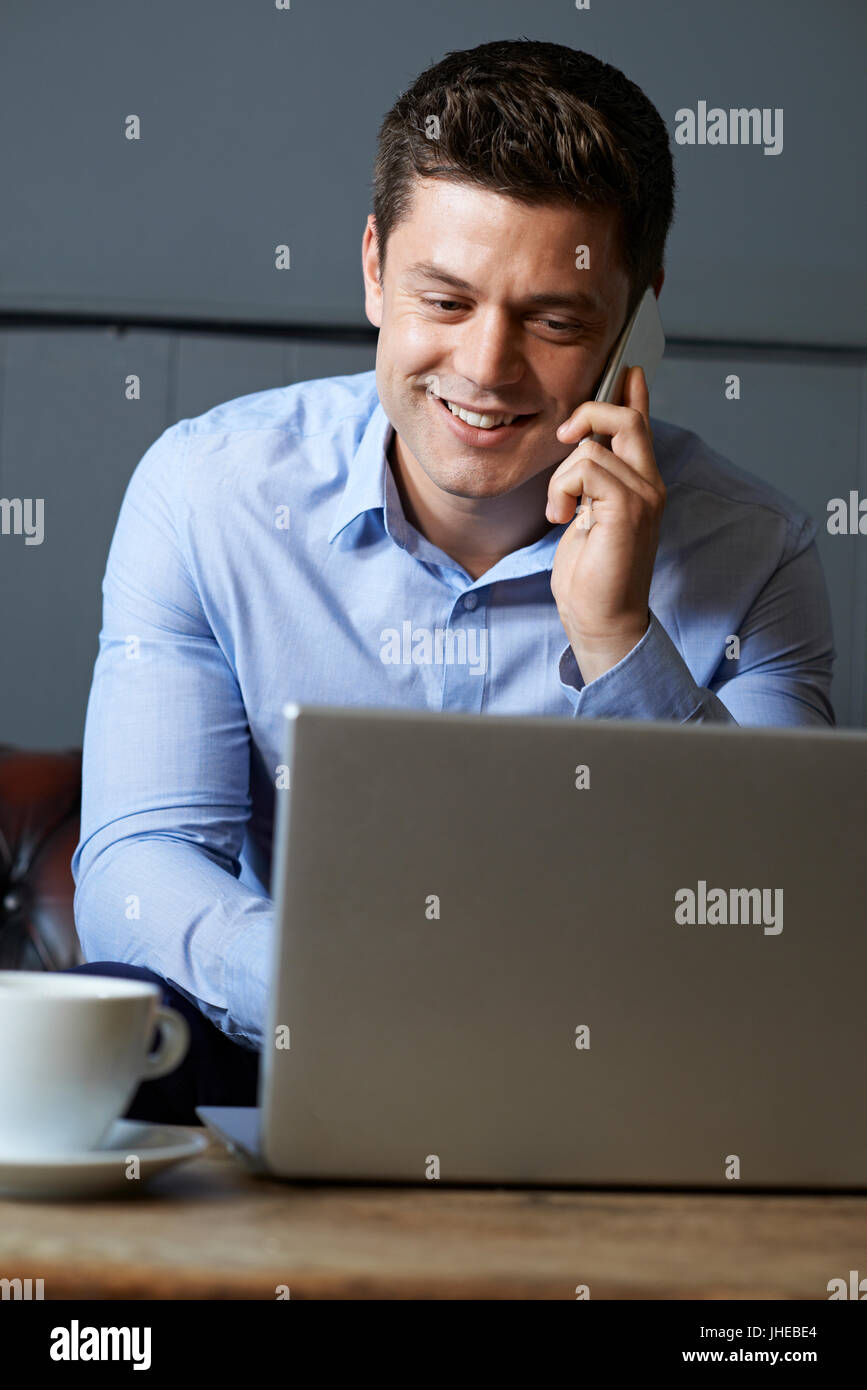 Businessman Talking On Mobile Phone Working On Laptop In Internet Cafe - Stock Image