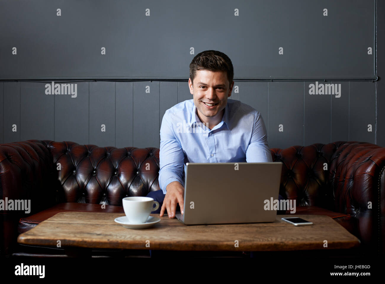 Portrait Of Businessman Working On Laptop In Internet Cafe - Stock Image
