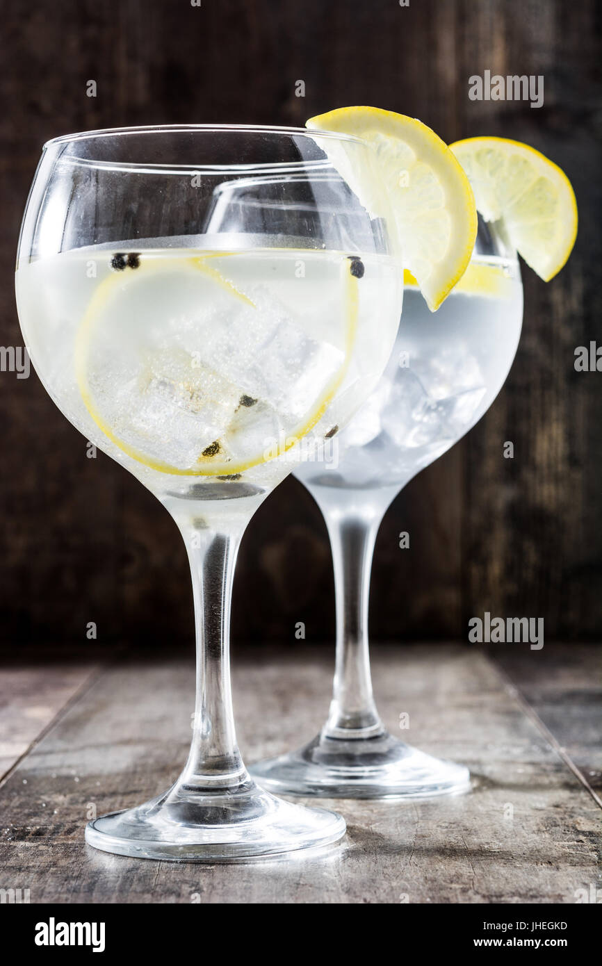Glass of gin tonic with lemon on wooden background - Stock Image