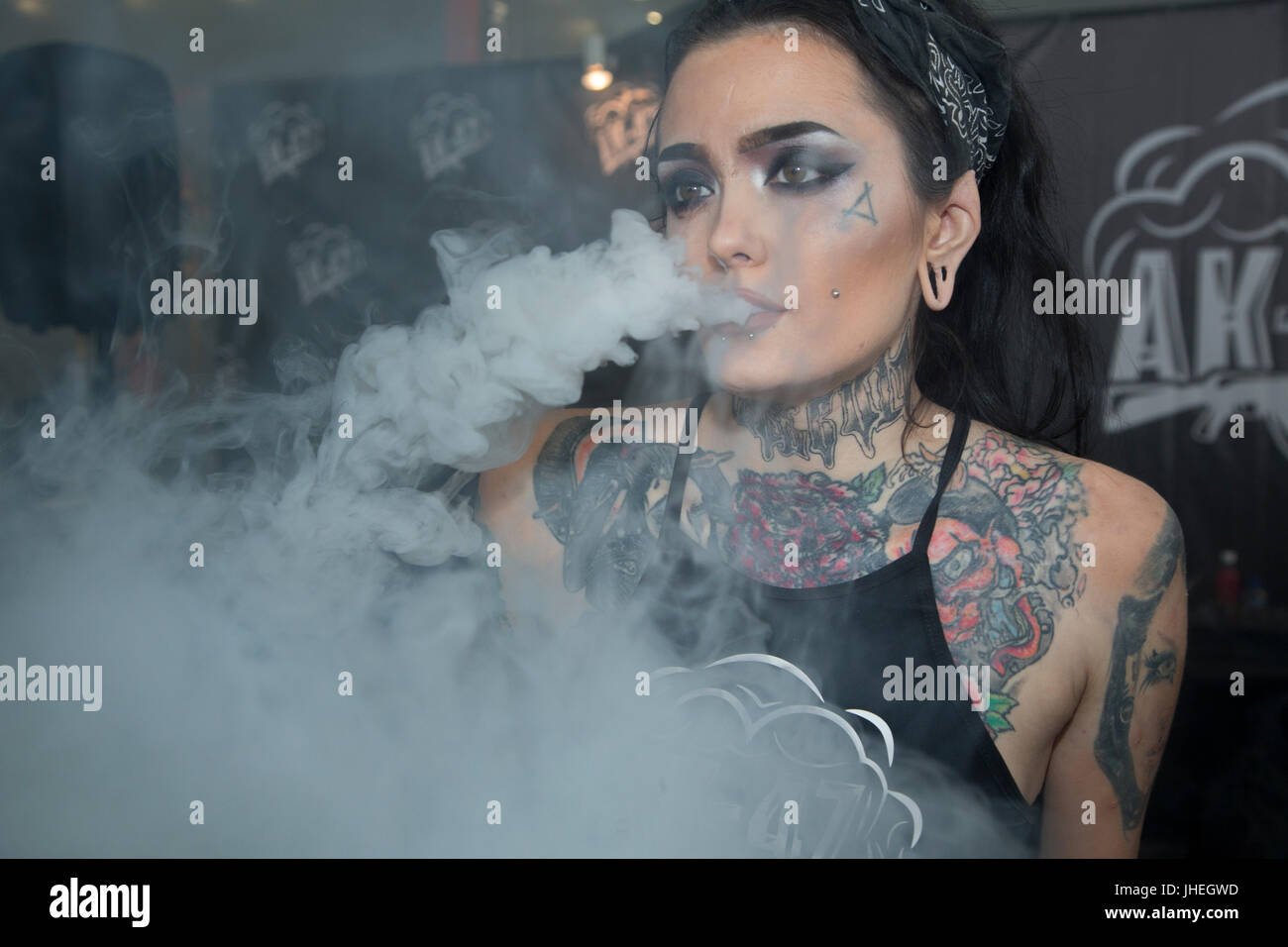 A woman smokes electronic cigarettes at the 'Vape Show' exhibitionin  in Moscow, Russia - Stock Image