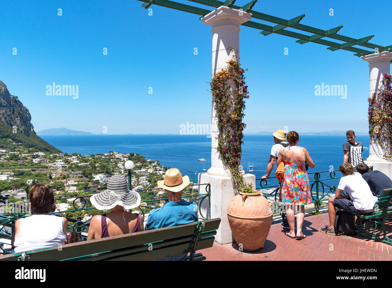 visitors to the island of capri in the gulf of nalpes italy, admire the view from above marina grande. - Stock Image