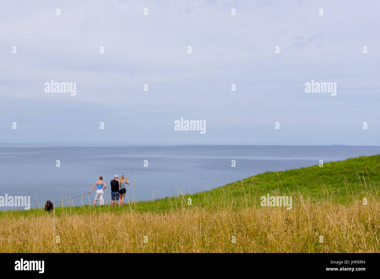 Family standing in the grass high above  the sea, Hundested, Denmark, July 10, 2017 - Stock Image