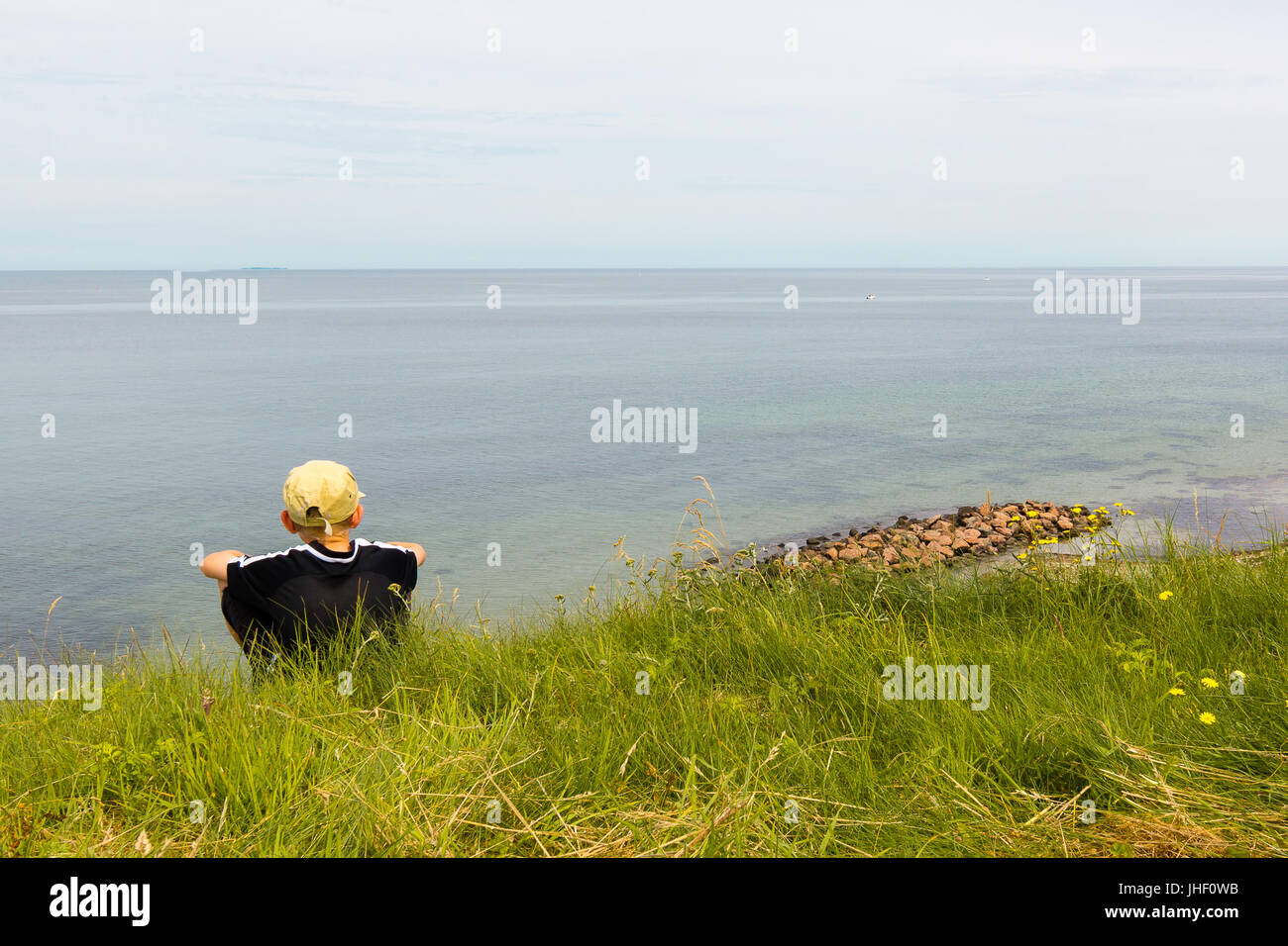 Boy sitting on te edge of a scarp, high obove the sea, Hundested, Denmark, July 10, 2017 - Stock Image