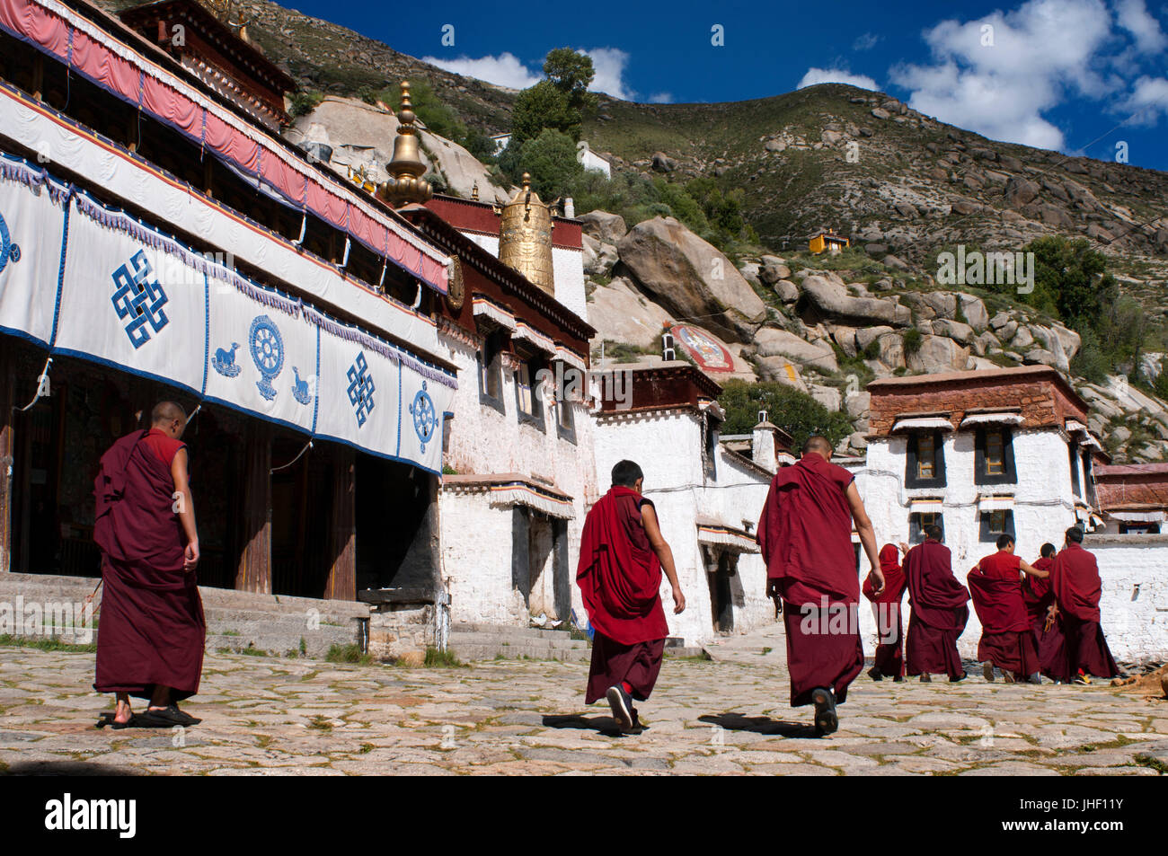 Monks outside of the Sera Monastery Temple, Lhasa, Tibet. The monastery of Sera, in Lhasa, is known for the discussions - Stock Image