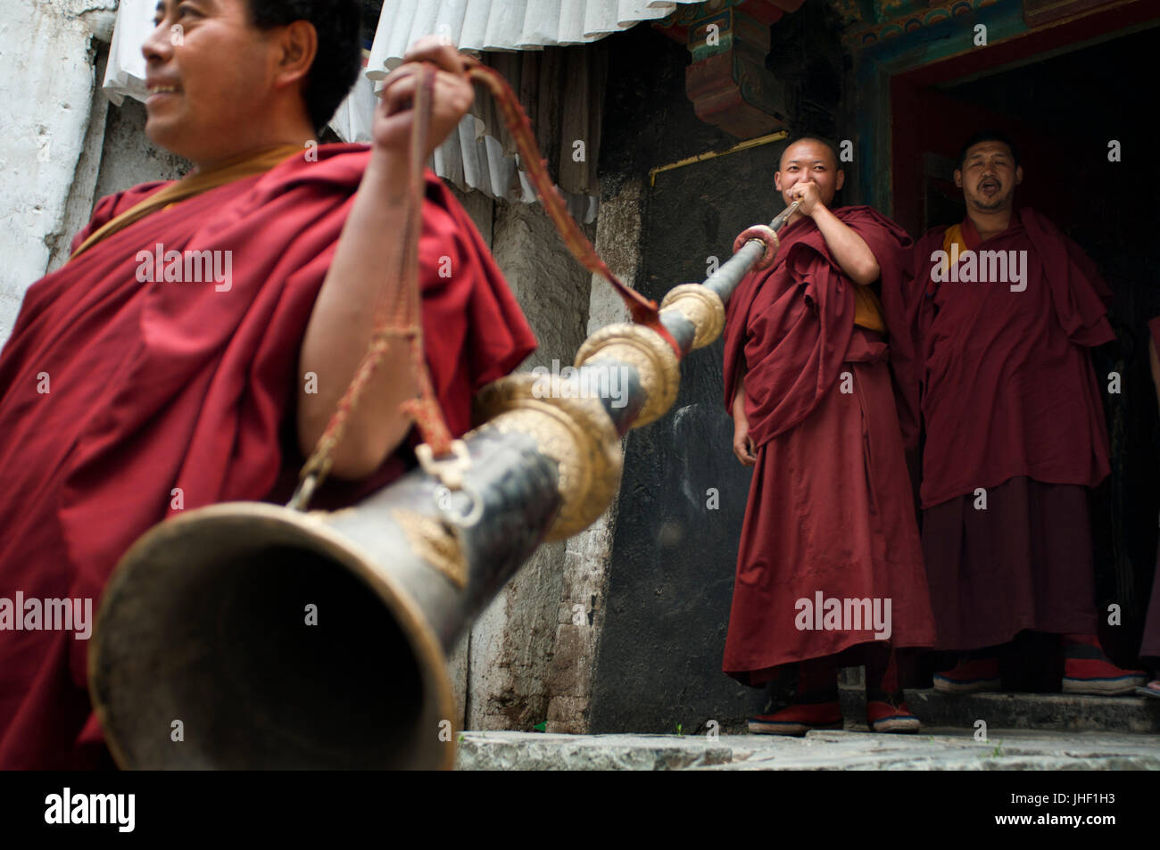 Monks playing the Tibetan horn inside Tashilumpo Monastery at Shigatse, Tibet, China. - Stock Image