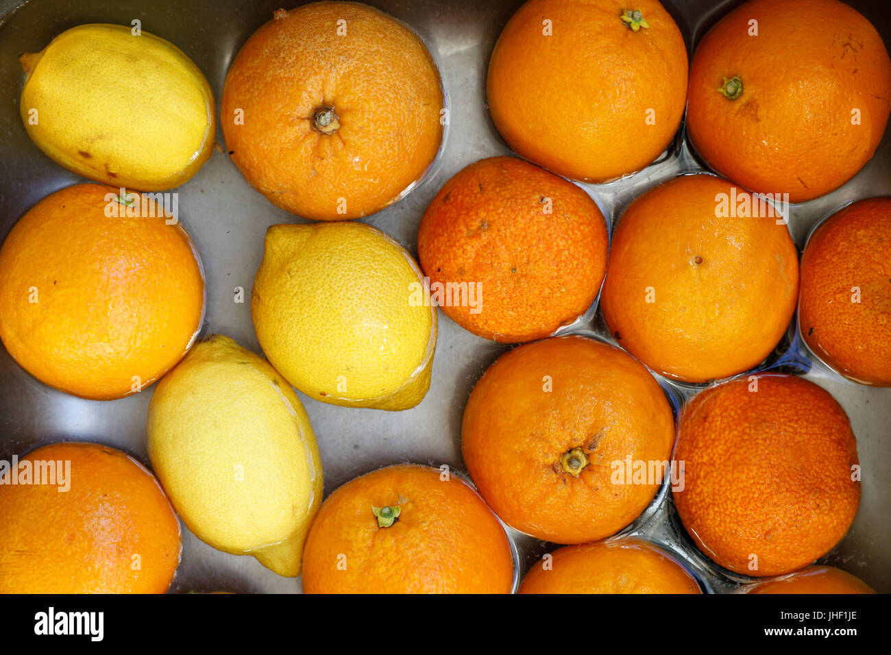 Oranges and lemons being washed in water in stainless steel sink - Stock Image
