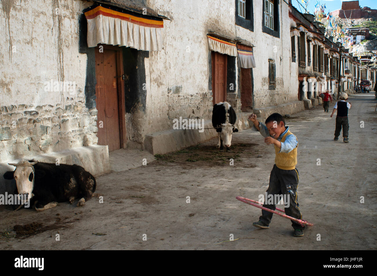 Two children play in the streets of the old town of Gyantse. Gyantse village, Tibet, China. - Stock Image
