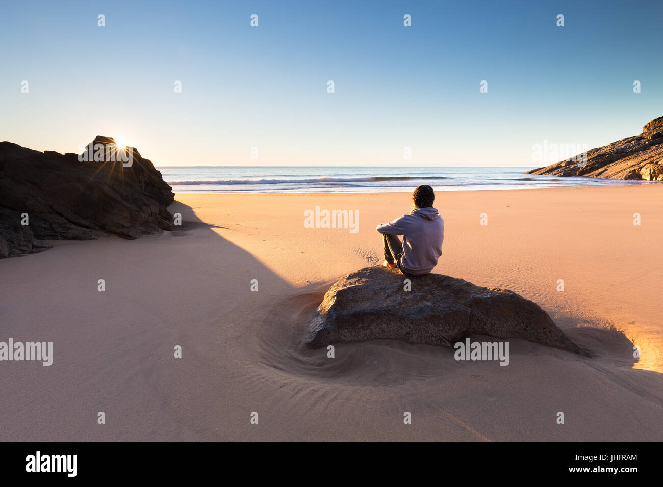 A person sits on a beautiful remote beach in Australia and watches a crisp sunrise over the ocean. - Stock Image