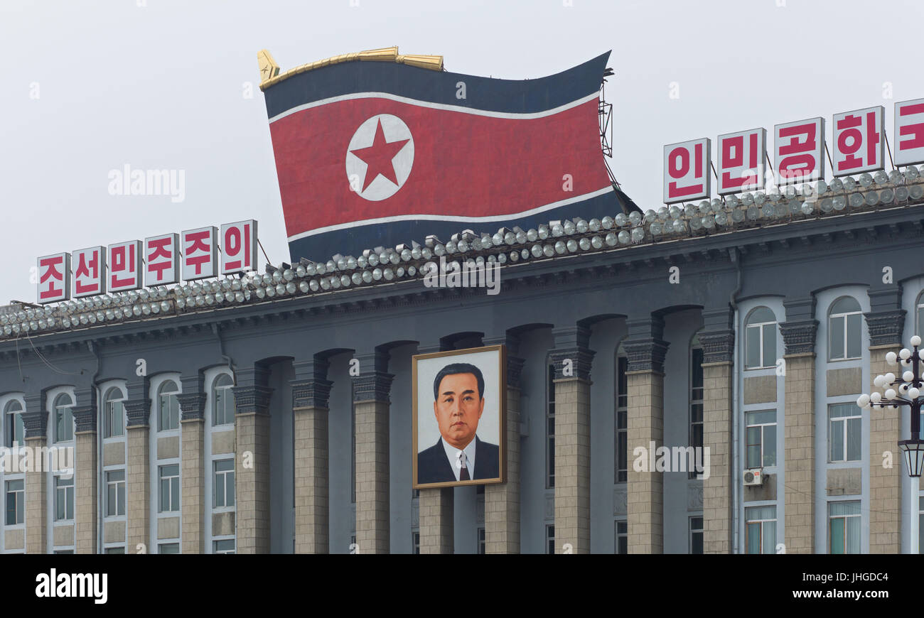Buildings around Kim Il-Sung square with patriotic slogans, North Korean flag, and portrait of Kim Il-Sung. Pyongyang, - Stock Image