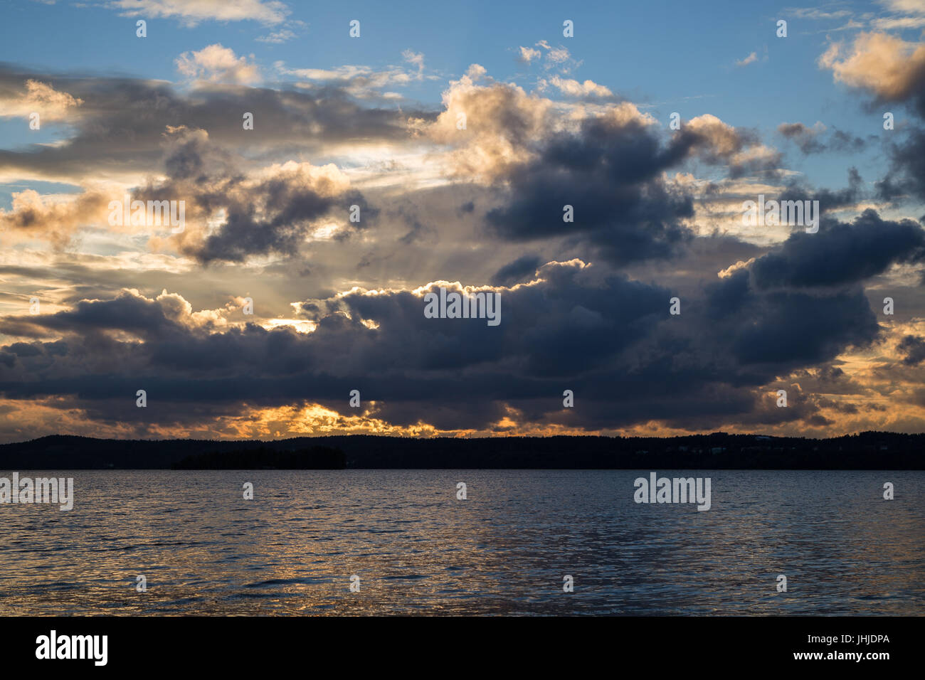 View of dark and dramatic clouds and a lake at sunset in Finland in the summer. - Stock Image