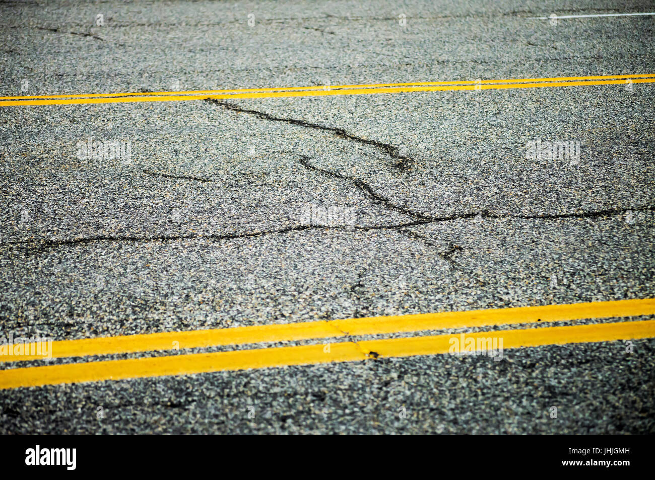 A section of cracked pavement with traffic lines. - Stock Image