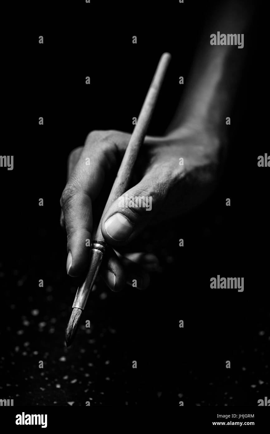 The artist's hands hold a brush. On a black background with deep shadows and bright highlights. Black and white - Stock Image