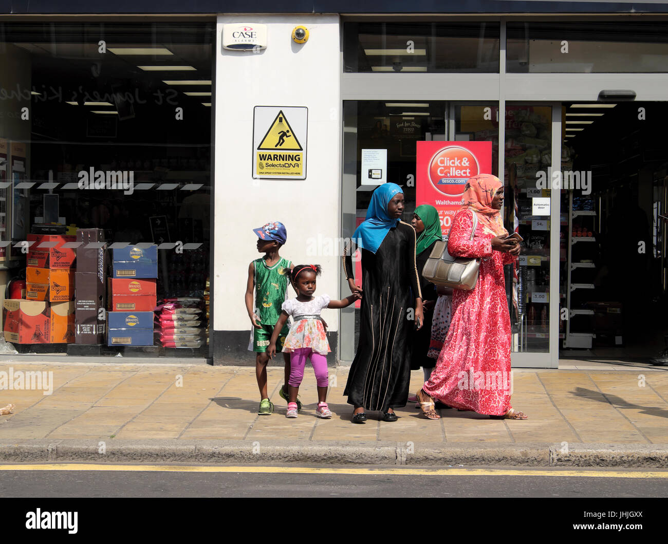 Muslim family mother daughters, children  waiting for a bus outside a store in London UK  KATHY DEWITT - Stock Image