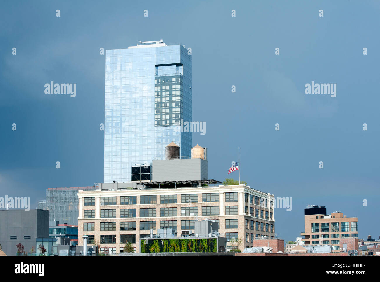 Looking across the rooftops of Tribeca to the Trump Soho hotel near which a U.S. flag flew at half mast because - Stock Image