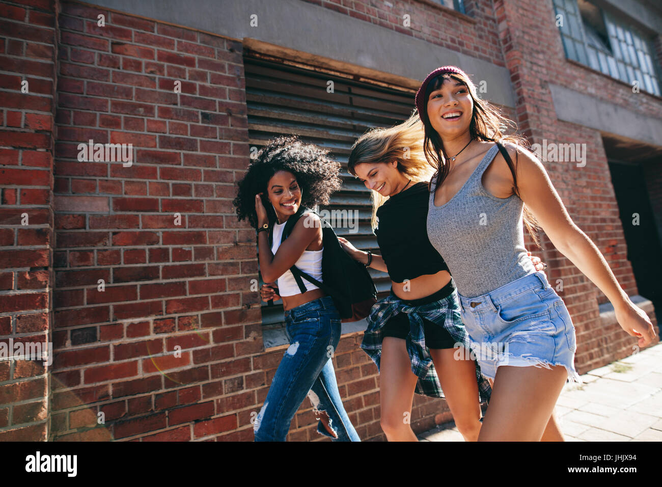 Multiracial group of friends walking down the city street. Three young women walking outdoors on road. Stock Photo