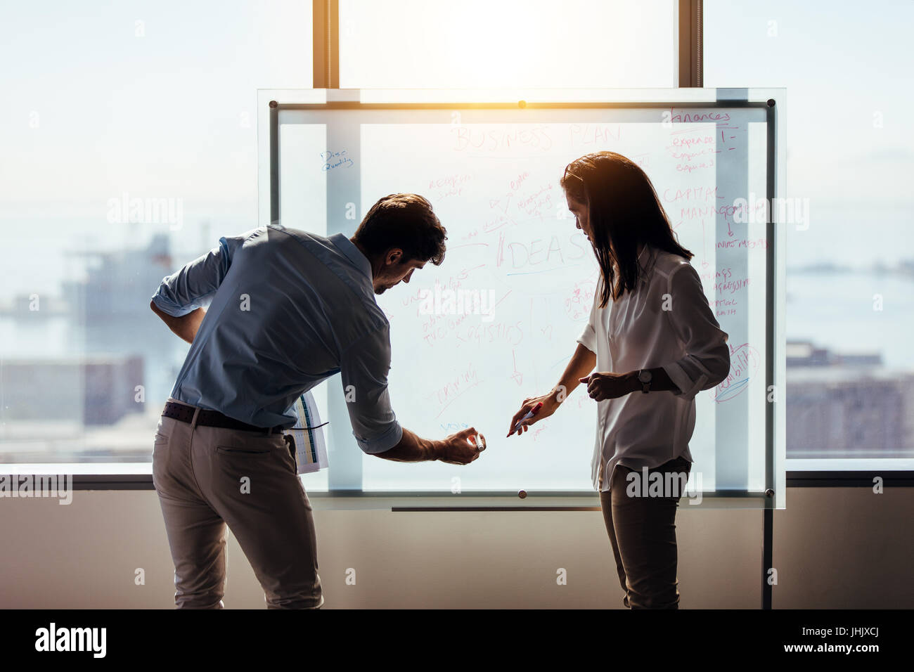 Man and woman entrepreneurs writing business ideas on whiteboard. Business investors discussing business ideas in - Stock Image