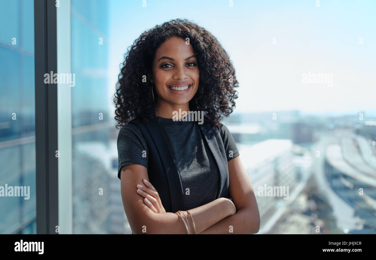 Closeup of a smiling businesswoman standing by the window of her office. Young woman with curly hair and arms crossed - Stock Image