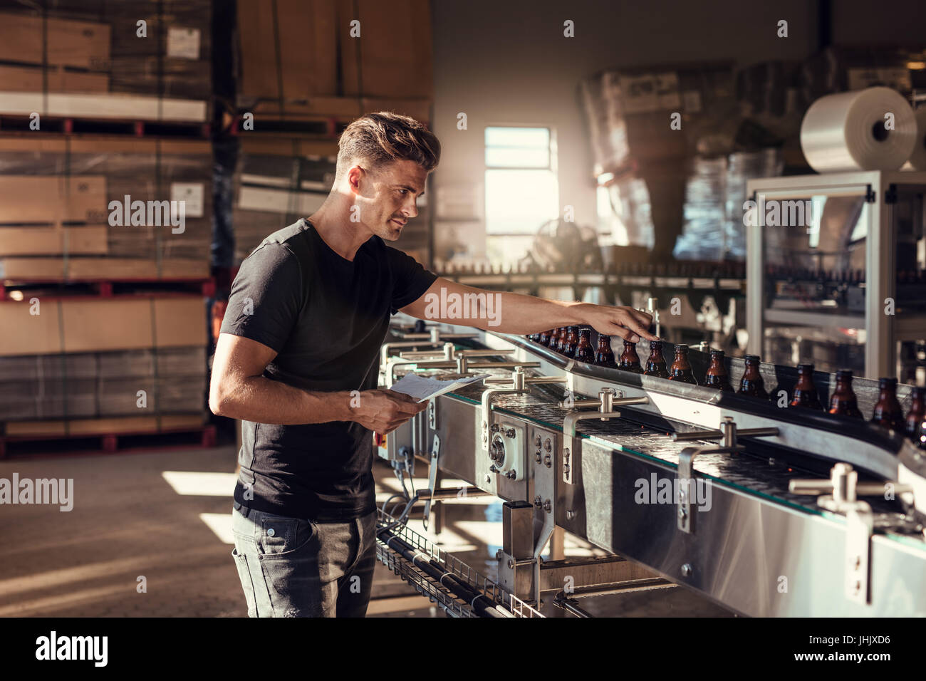 Young man supervising the beer production at brewery. Man working at alcohol manufacturing factory. His is standing - Stock Image