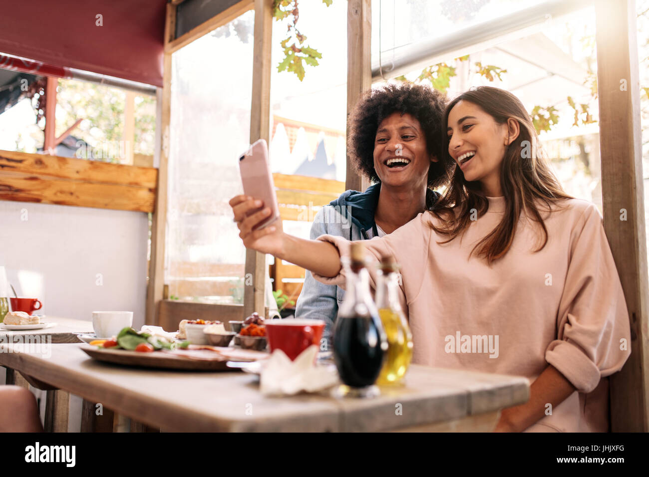 Cheerful woman taking selfie with her friend at cafe. Couple having fun using smartphone at coffee shop - Stock Image