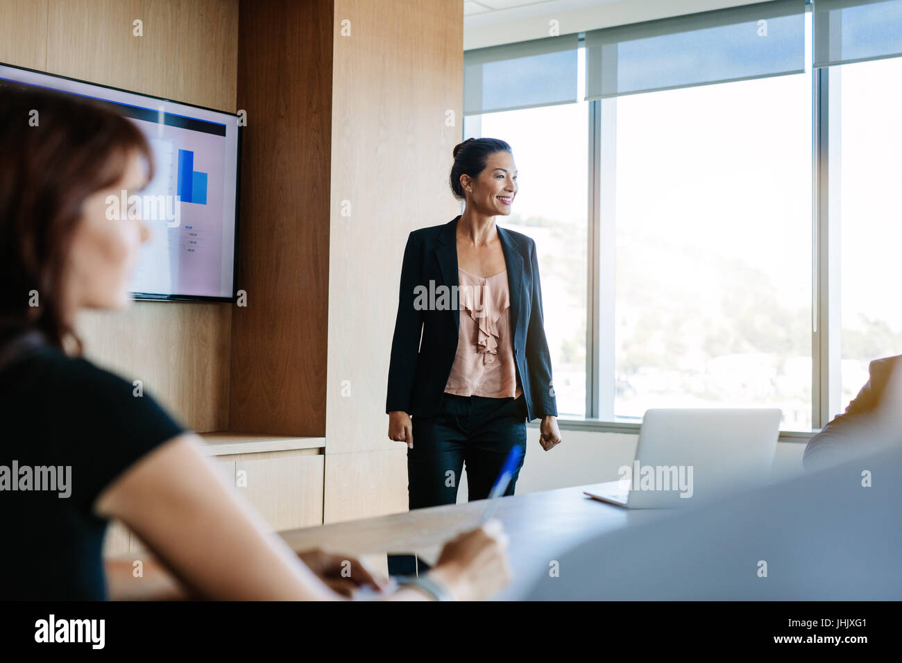 Asian businesswoman explaining plans to colleagues in conference room. Business presentation in board room. - Stock Image