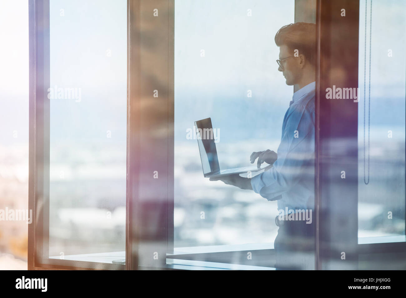 Horizontal shot of mature businessman standing at window and using laptop. Business professional standing inside - Stock Image