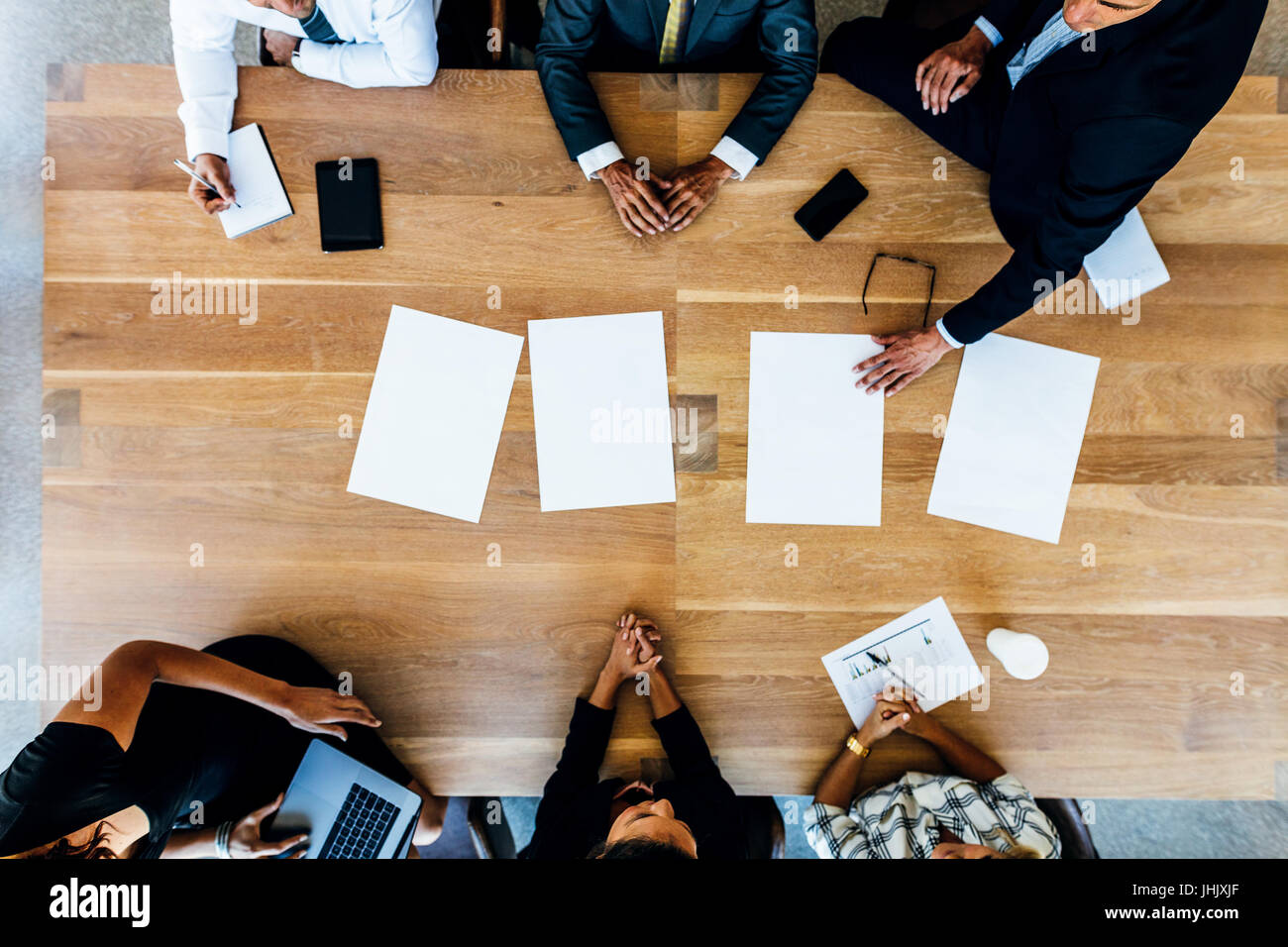 Top view of business people sitting around a table with blank sheets. Multi ethnic business professionals in meeting. - Stock Image