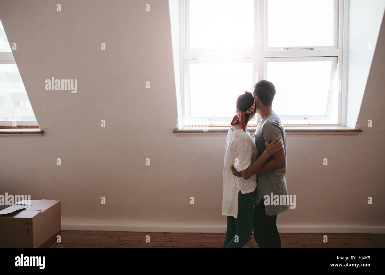 Loving young couple moving in a new apartment. Man and woman standing together with boxes on floor. - Stock Image
