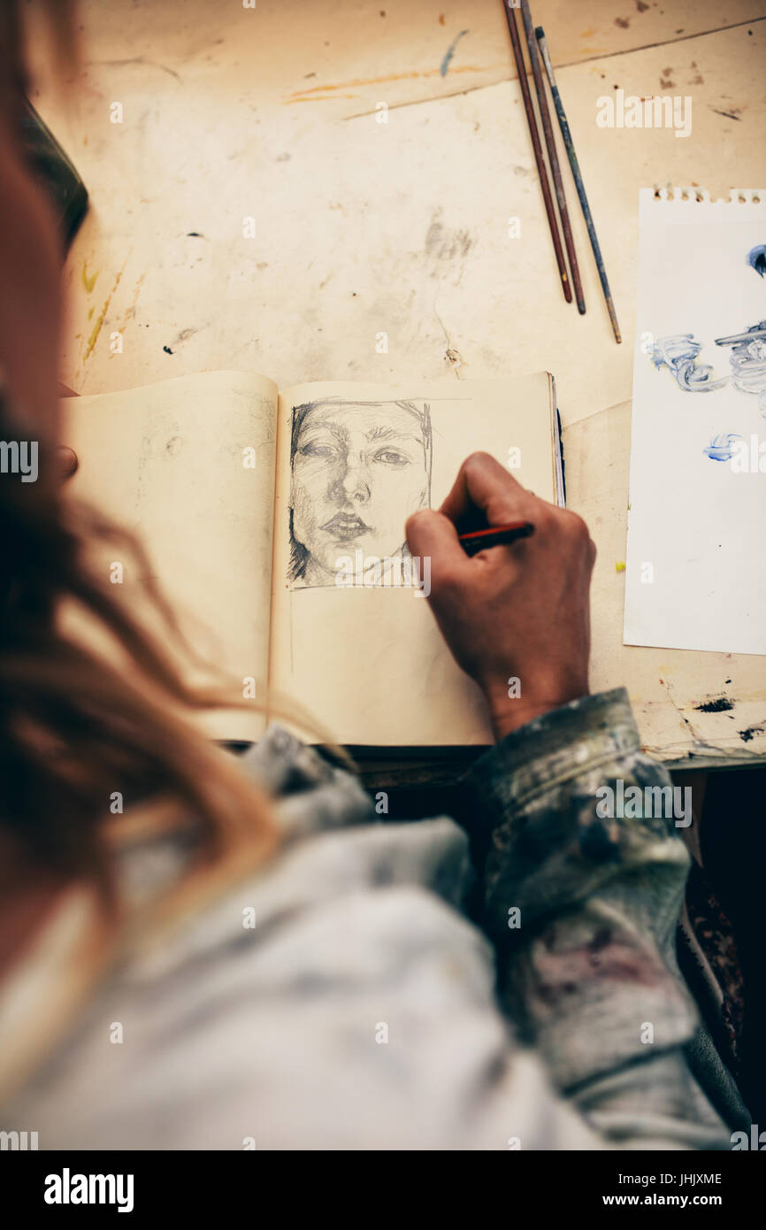 Top view of woman artist sketching on book in her studio. Close up of female painter working in her workshop. - Stock Image