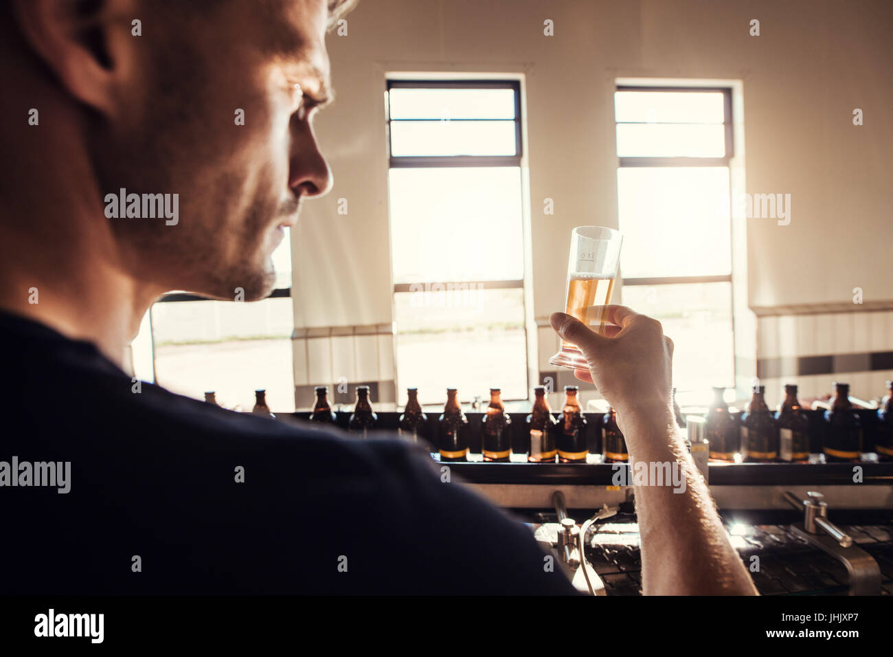 Male brewer testing craft beer at brewery factory. Young man examining the beer sample glass during manufacturing. - Stock Image