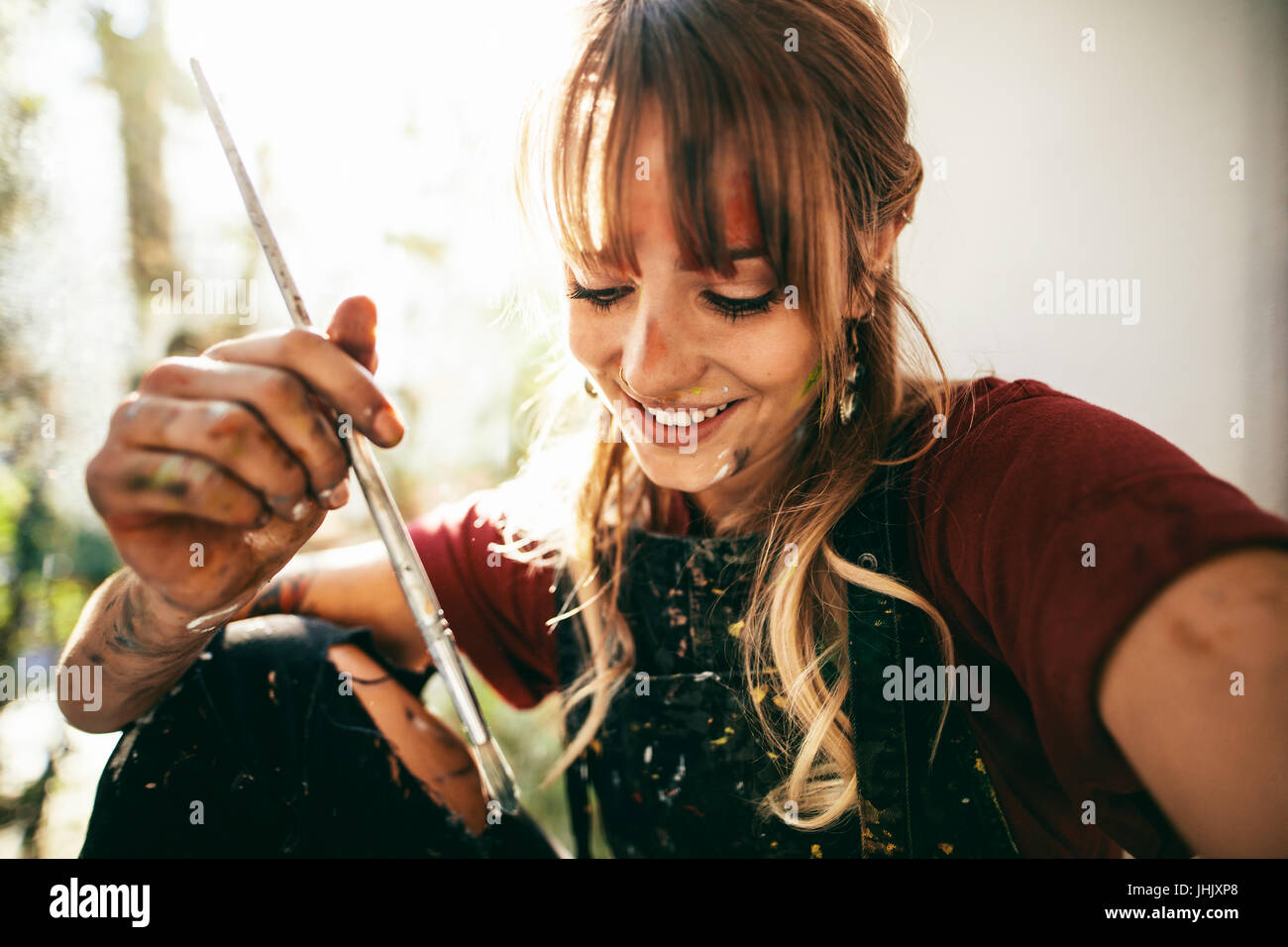 Close up of beautiful young caucasian woman artist with paint brush. Female painter holding brush and smiling. - Stock Image