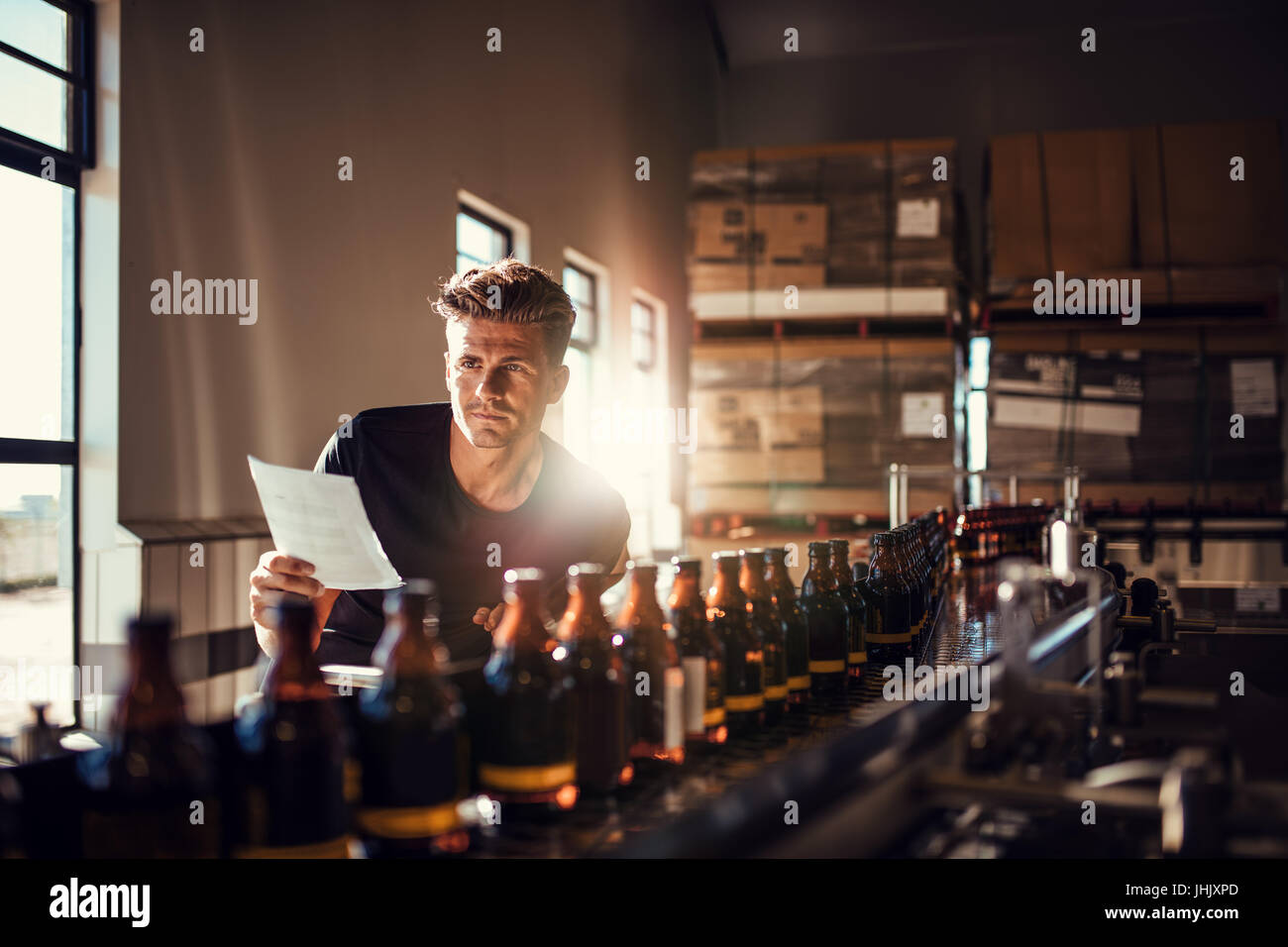 Young man supervising the process of beer manufacturing on brewery factory. Factory worker checking the process - Stock Image