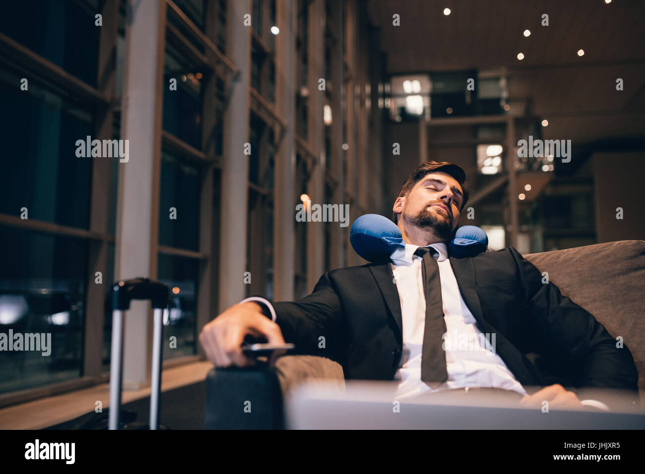 Traveler waiting at airport after flights delays and cancellations. Businessman asleep in airport lounge. - Stock Image
