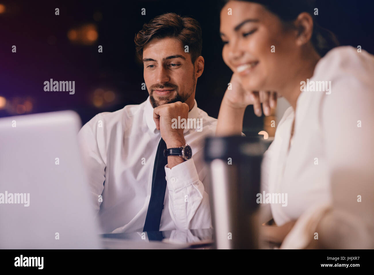 Business man and woman sitting at table and looking at laptop. Business people waiting at airport lounge using laptop - Stock Image
