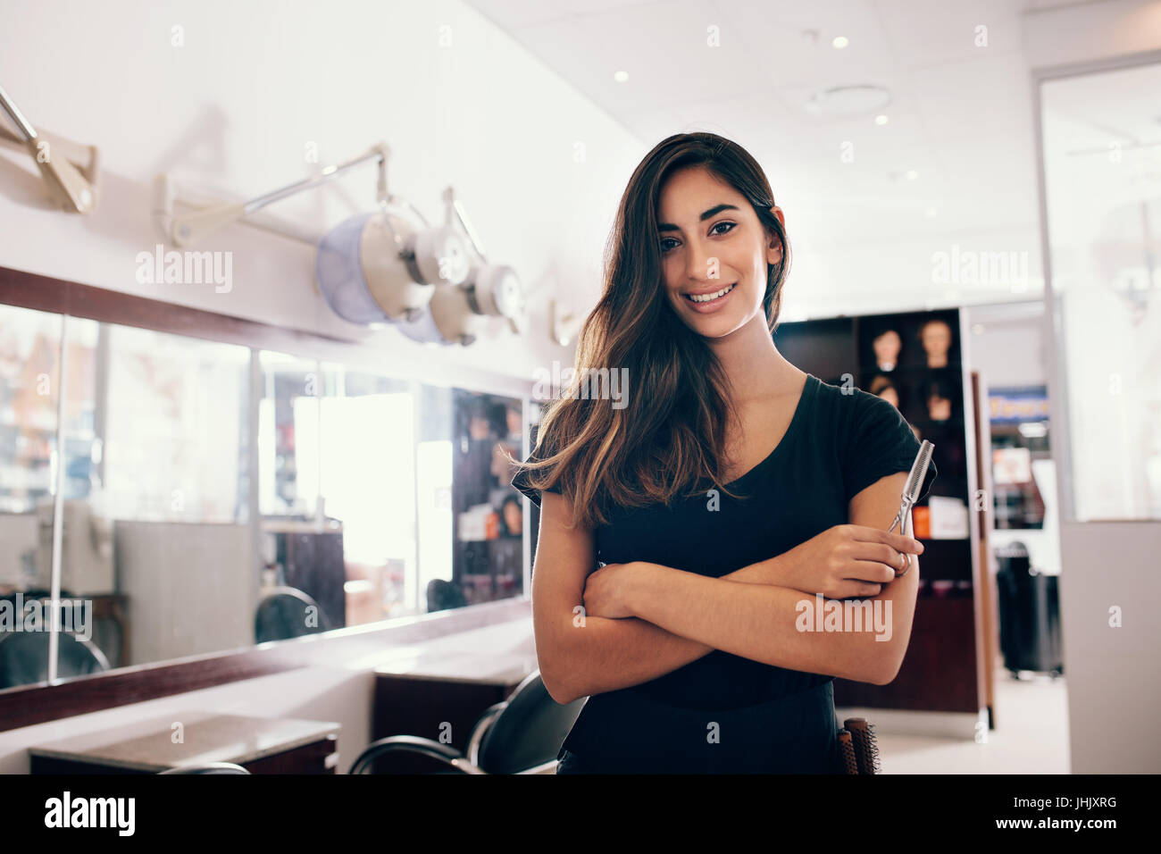 Professional woman hairdresser in salon with scissors in hand. Smiling young woman standing in salon with folded - Stock Image