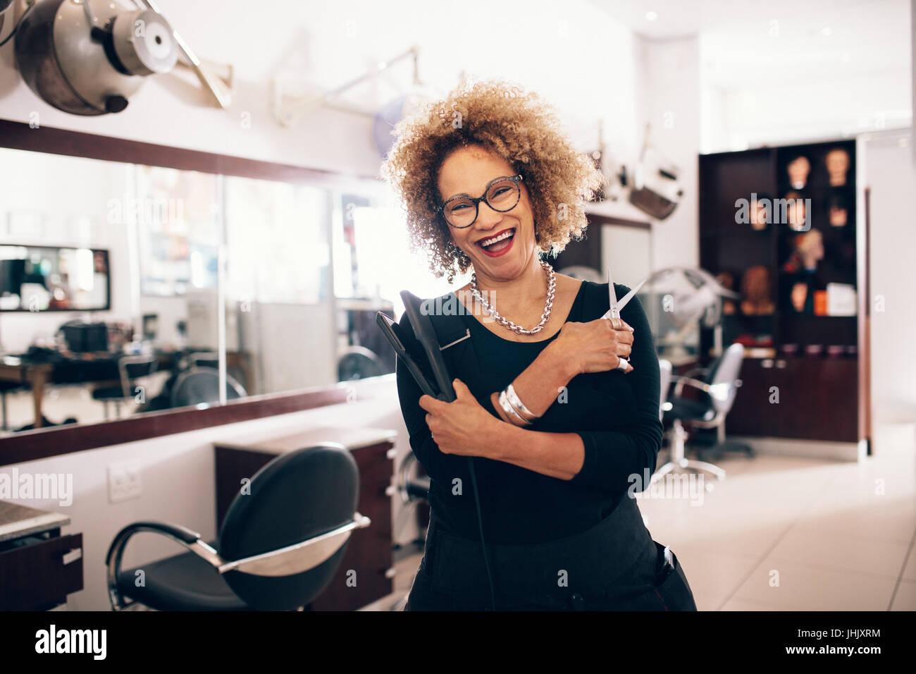 Smiling female hairdresser holding a hair straightener and scissors. Well equipped beauty salon with professional - Stock Image