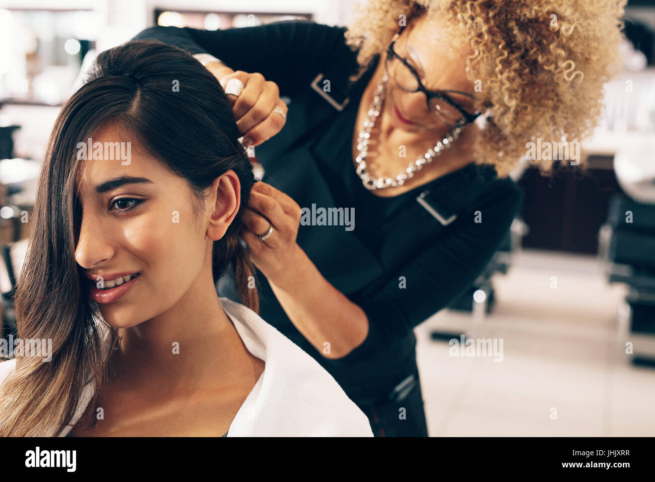 Closeup of a woman getting a stylish hairdo done at salon. Professional hair stylish pinning up the hair in stylish - Stock Image