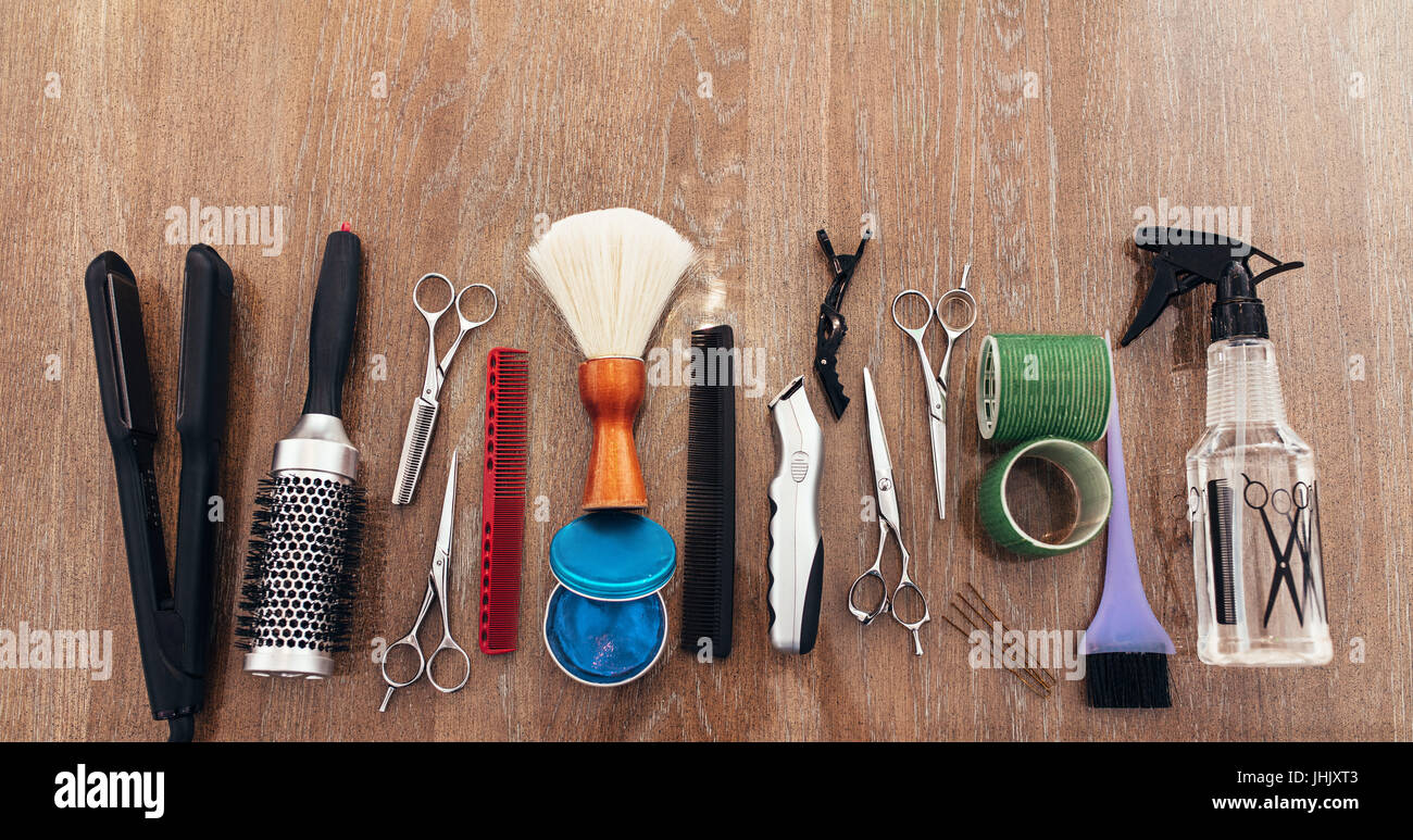 Professional hairdresser tools on wooden surface. Top view of hairdresser accessories arranged in line. - Stock Image