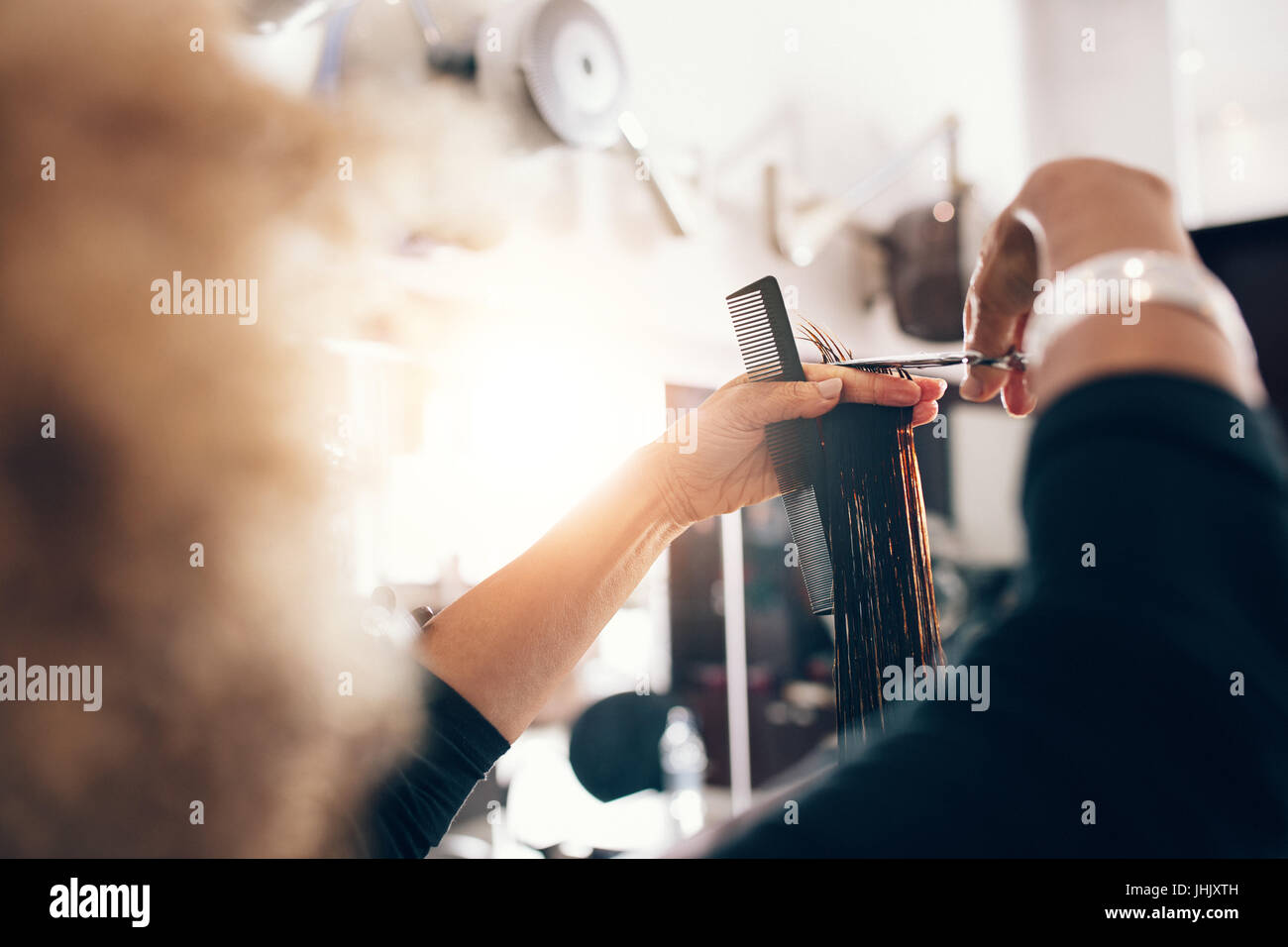 Hairdresser holding a strand of combed hair in between her fingers. Hairstylist cutting hair in a level. - Stock Image