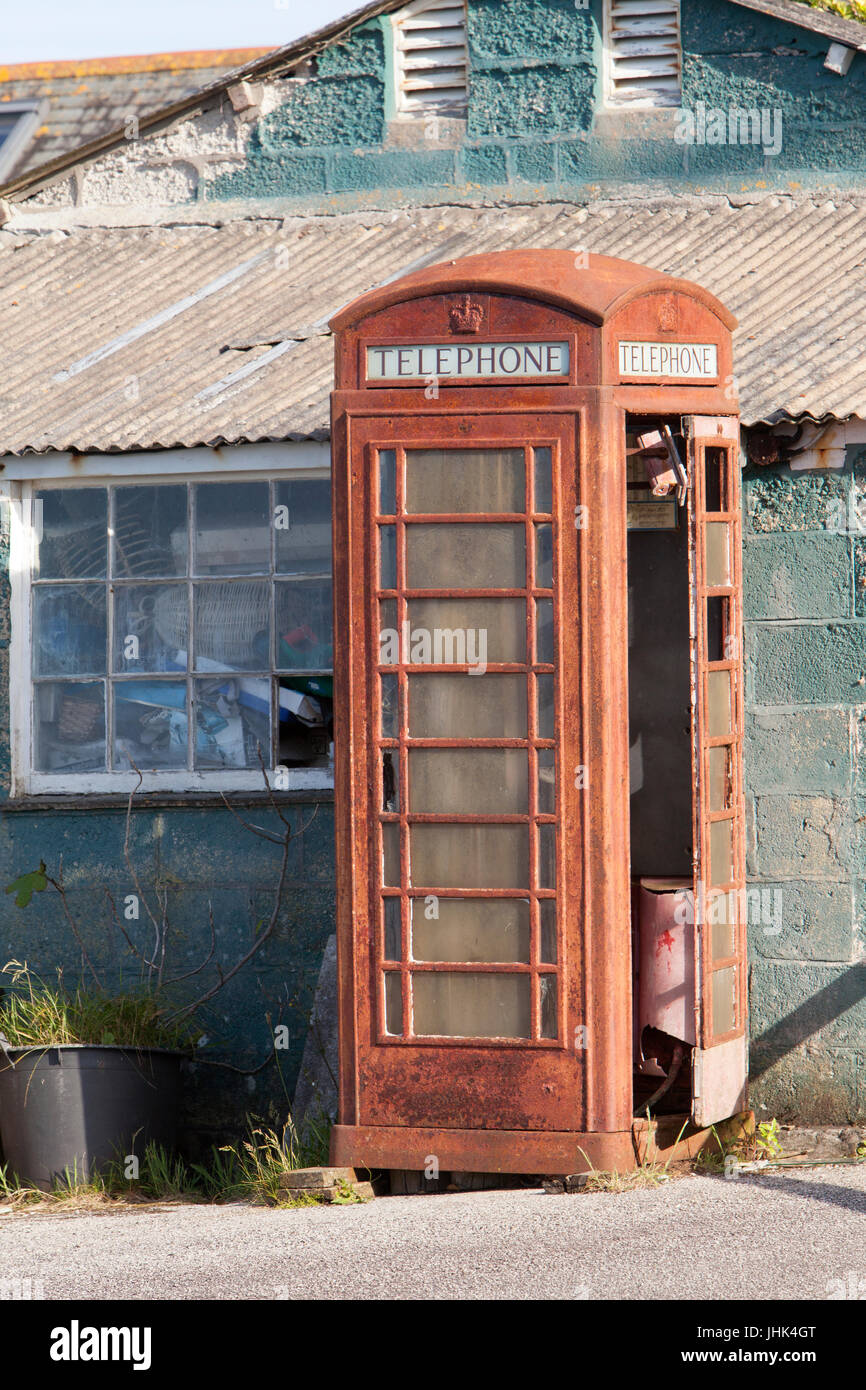 An old disused abandoned and unloved red phone box stands derelict next to a scruffy looking building - Stock Image